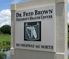 Dr. Fred Brown - Sign faces with flat-cut decoration on existing monument structure